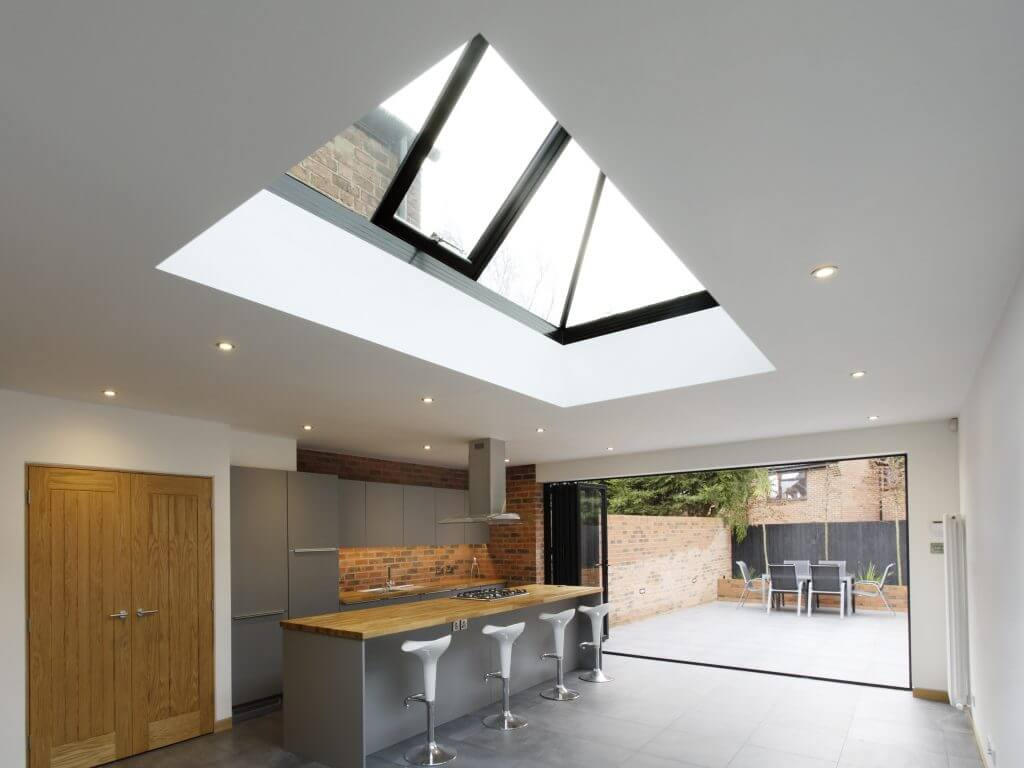 Bi-fold doors opening onto a contemporary garden, with a vented lantern above